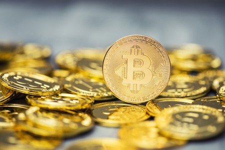 A pile of golden bitcoins on a solid backdrop Stock Photo