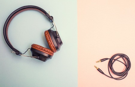 Beautiful brown headphones with folded wireon a dual background Stock Photo