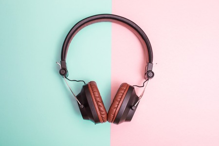 Fancy headphones laying on a flat pink and blue surface. C