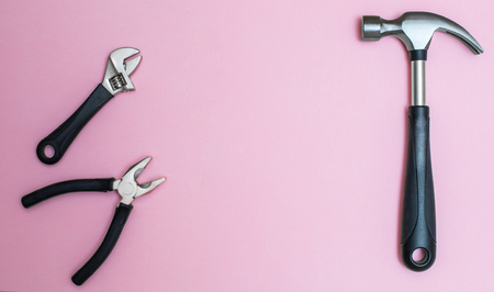 Working tools: hammer and pliers on pink, creative background for custom diy message.