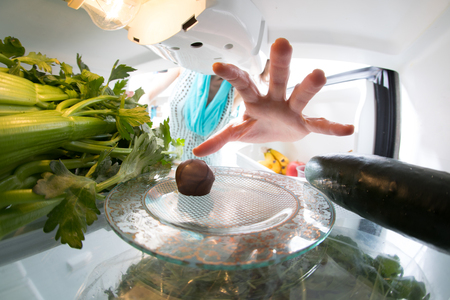 Diet struggle: A hand grabbing a tiny candy from the open refrigerator full of greens. Stock Photo