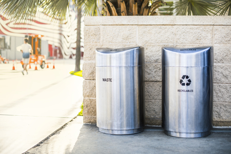 Separate garbage bins for recycled trash and waste installed on a sidewalk on the city street