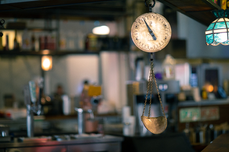 Classic Vintage copper scale in an old marketplace interior shot in Grand Central Market, Los Angeles with a picturesque blurred background Archivio Fotografico