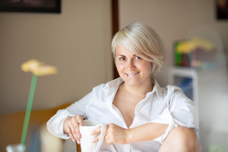 Playful cute blond girl biting her lip sitting cozy at the table in apartment Banque d'images - 106355642