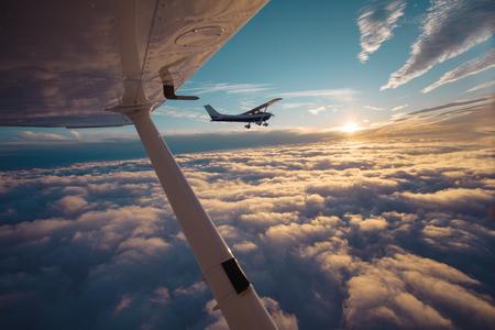 Pequeño avión monomotor volando en el hermoso cielo del atardecer a través del mar de nubes