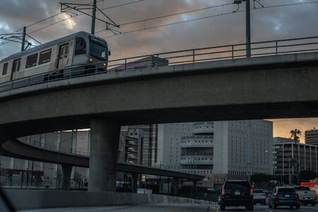 Los Angeles, USA, March 2018: Los Angeles transportation system: 101 freeway evening traffic and an open high rise metro railroad on a ramp