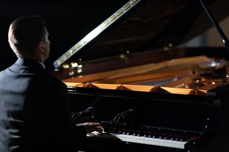 An elegant man in a black suit playing grand piano on stage in a concert hall, close up, unrecognizable.