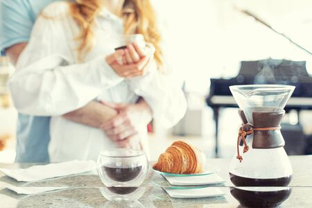 A young couple cuddling in the kitchen, pour over coffee maker on the front plan, coffee commercial Banque d'images - 130060726