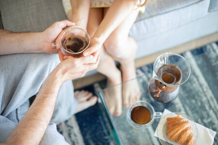 A couple holding cup of coffee together: ideal morning at home. No faces in the shot. Stockfoto