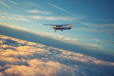 The round curve of the earth covered by golden clouds and a sall single engine airplane flying in the sunset