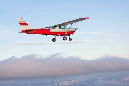 Simpatico aeroplano Cessna che vola via su un terreno collinare coudy
