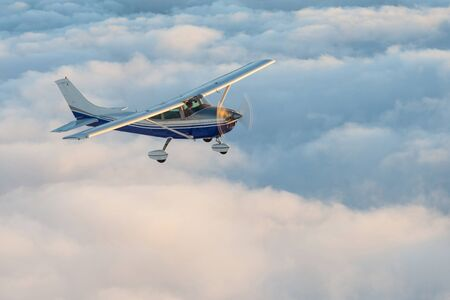 Stunning view of a blue and white little private Cessna airplane browsing the sky over fluffy fairy tale clouds. 免版税图像