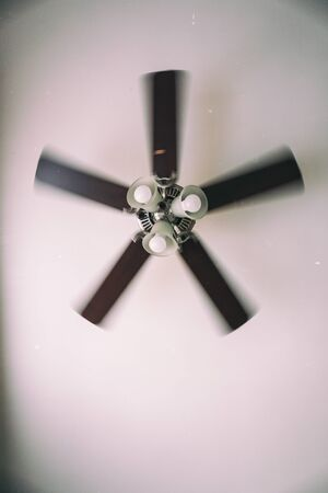 A vintage photo of an old electric ceiling fan installed into a ceiling lamp