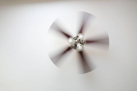 A working ceiling fan on a white ceiling, close up with blurred fan blades, three lamps, daytime. 스톡 콘텐츠
