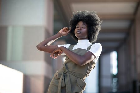 Fashionable African American girl in downtown wearing fancy overalls and white turtleneck