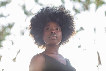 Young african american woman shot from below, confident look, determined 写真素材