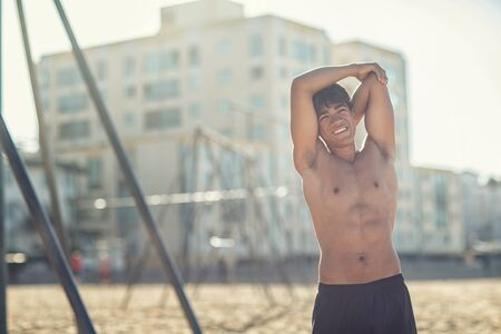 Portrait of a handsome young muscular man in swimwear on the muscle beach at Santa Monica next to fitness equipment