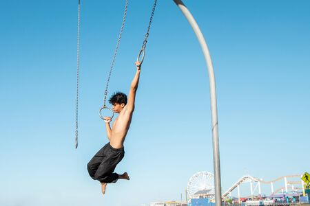A young man athlete working out on traveling rings on muscle beach, Santa Monica, California