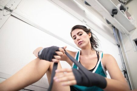 A woman boxer wrapping her hands in wraps in the gym getting ready for a class, shot from below, white garage door background 版權商用圖片