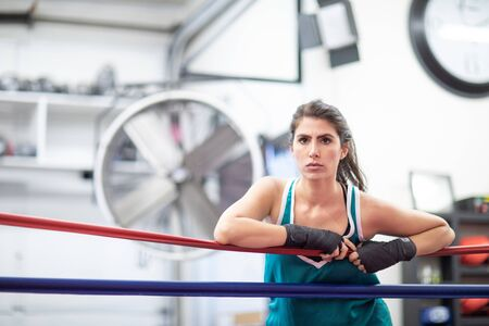 A badass female boxer is resting on ring ropes with her wraps on in a boxing gym, white walls, black and red mats.