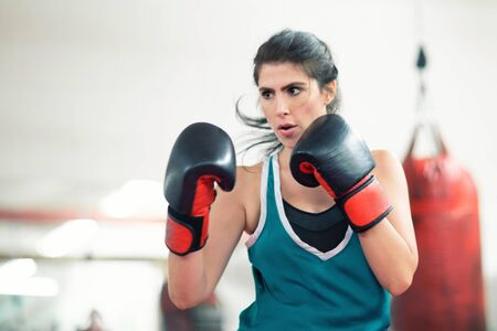 A young female boxer punching a bag in the gym