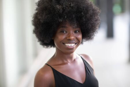 Gorgeous looking young black girl smiling broadly looking at the camera, dental service commercial