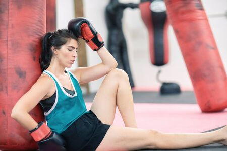 Female boxer sitting on the mats leaning on the boxing bag, resting after a workout