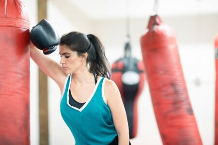 Female boxer taking a break, tired after a workout, leaning her elbow on a boxing bag