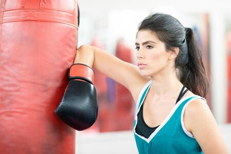 Female boxer leaning on a boxing bag, looking confidently in front of her