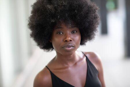 Young beautiful stylish curly woman on the street. Closeup.