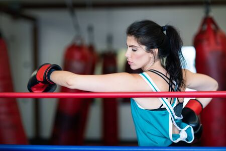 A young woman girl is hanging on the ropes of a boxing ring, resting, wearing boxing gloves.