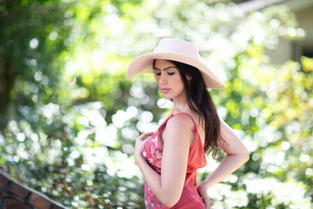 Portrait of a beautiful young Italian woman wearing a straw hat in sunny warm weather day.