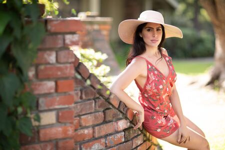 A hot young woman sitting on a designers red brick fence in front of a house, perfect for real estate and construction content