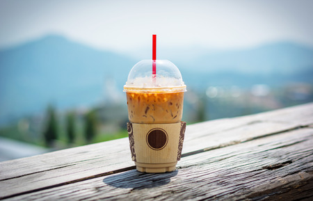 Mock up of a cup of cold coffee on wood table and had too soft focus nature behind