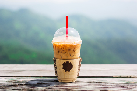Mock up of a cup of cold coffee on wood table and had blur nature background behind