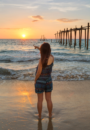 Woman stand and point to sunset on the Pi Leh bay in Thailand. This place you can see old wooden bridge that is landmark of Pi Leh bay.