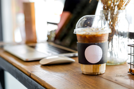 A plastic cup of cold coffee placed on wood table and Reklamní fotografie