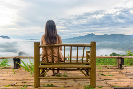 Girl sat on the bamboo chair and looking nice mist and nice landscape. Reklamní fotografie