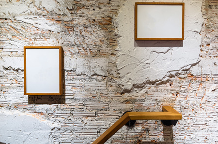 White broken wall in modern room and two frames were hanged on this wall. Reklamní fotografie