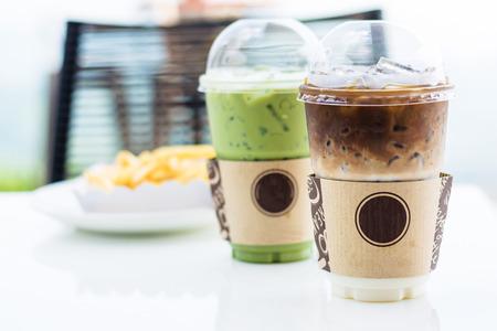 Mockup van een kopje koude koffie en groene thee latte op tafel met frietjes op achtergrond