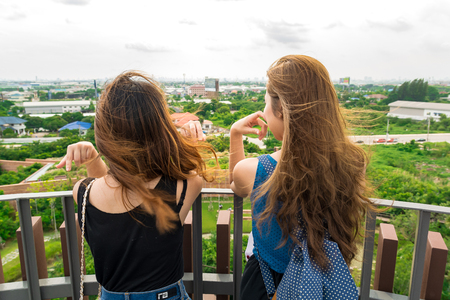 two girls talking on the tower with motion blur on their hair and looking forest in city