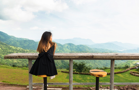 Girl sit on wooden chair and table for waiting someone with mountain and forest background. This place is Thailand. Reklamní fotografie