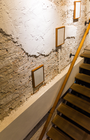 White broken wall in modern room and two frames were hanged on this wall beside with staircase. Reklamní fotografie
