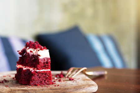 Red velvet cake was chipped on wooden plate with fork