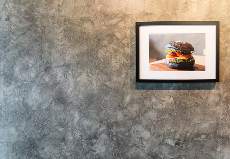 Single frame with chacoal burger picture on concrete wall Reklamní fotografie