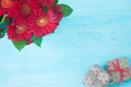 Red gerbera flowers with gift boxes on blue background Archivio Fotografico