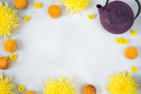 Mooncakes, tetera, flores de crisantemo sobre fondo gris con espacio de copia. Comida china del festival del medio otoño. Foto de archivo
