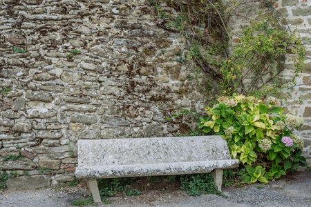 Ancient stone bench in a small village of medieval origin. Volpaia, Tuscany, Italy