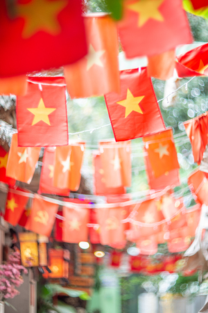 Blurred background of Vietnamese flags on the street.