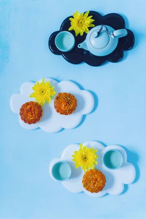 Mooncake, blue teapot, yellow chrysanthemum flowers. Chinese mid-autumn festival food. Stock Photo